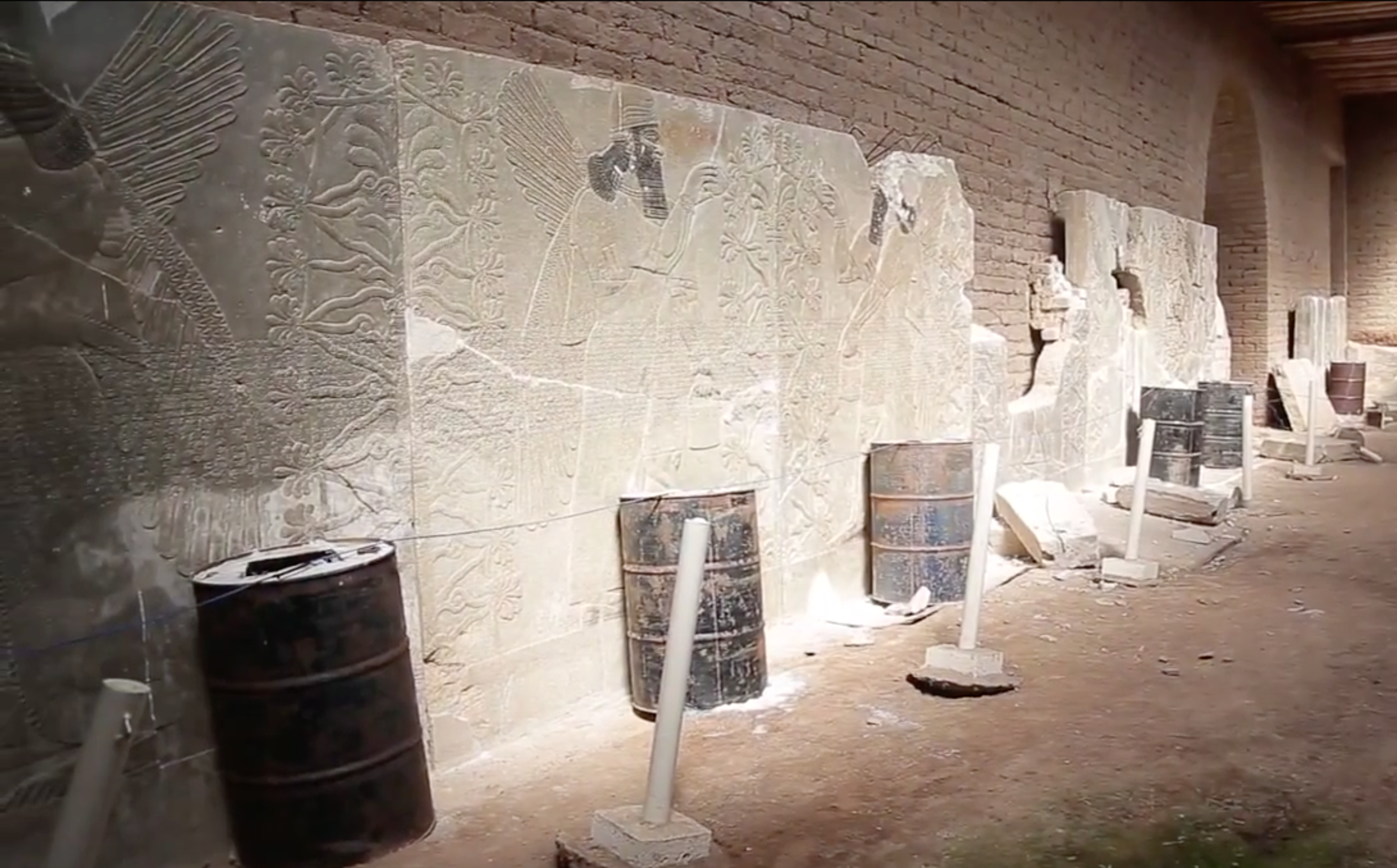 Nimrud, Northwest Palace, barrel bombs arranged in front of relief panels (still image from video released by ISIL on April 11, 2015)